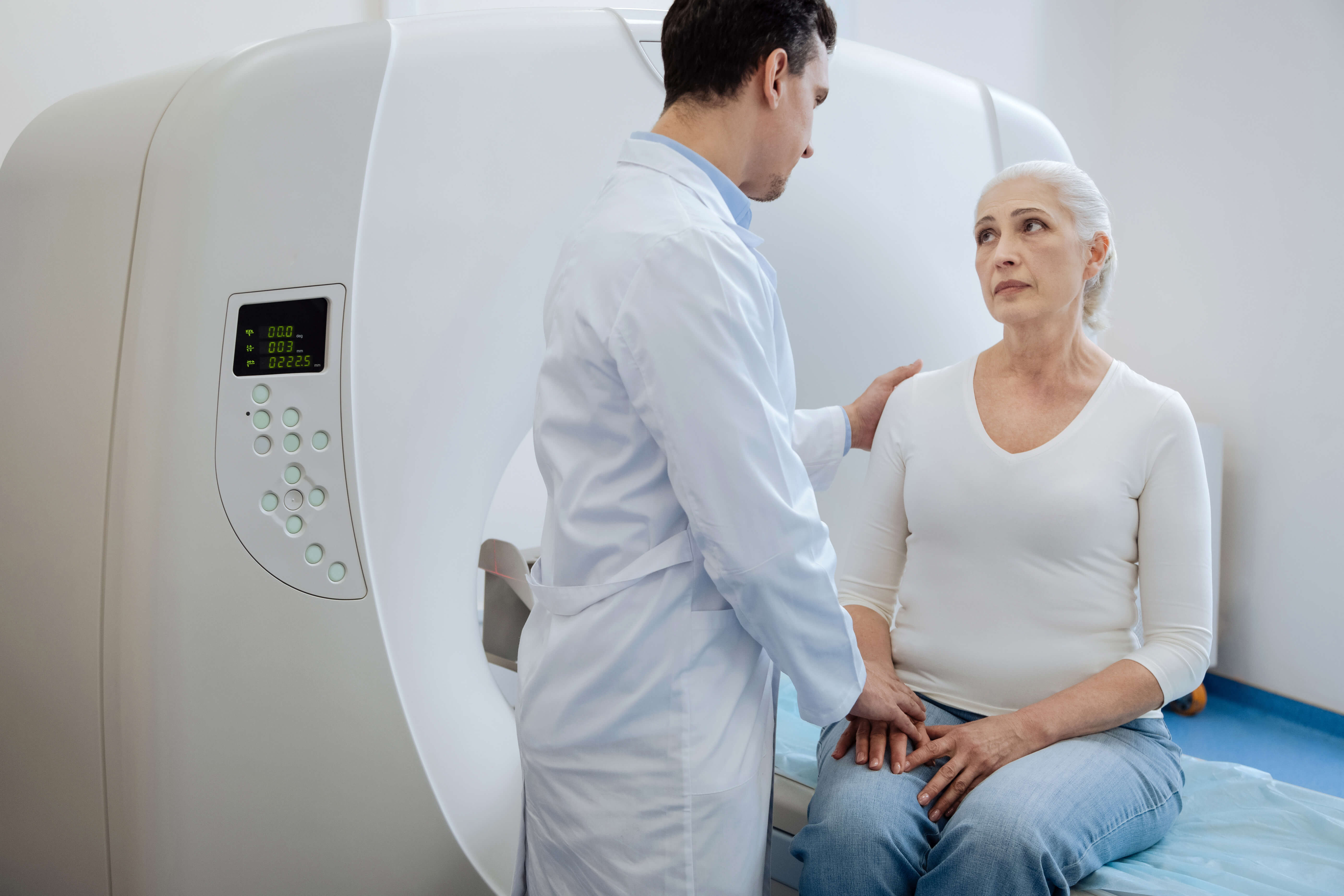 Professional oncologist putting his hand on the patients shoulder and supporting her while telling her the diagnosis